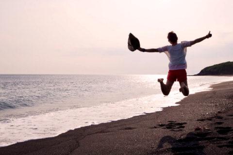 やさしいオレンジ色に染まった海と黒い砂浜〈伊豆大島 砂の浜〉